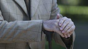 Viejas manos masculinas que inclinan el bastón, ayuda social de pensionistas, incapacidad almacen de metraje de vídeo