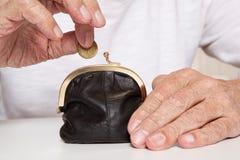 Viejas manos mayores que sostienen la moneda y la pequeña bolsa del dinero imágenes de archivo libres de regalías