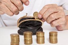 Viejas manos mayores que sostienen la moneda y la pequeña bolsa del dinero fotos de archivo
