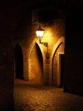 Viejas pared de ladrillos rojos y ejecución de la luz en la pared noche arco Fortaleza Imagen de archivo libre de regalías