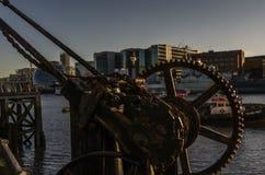 Viejas piezas oxidadas de la grúa costera en los bancos del río i Foto de archivo libre de regalías
