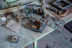 Viejas placas de circuito eléctricas soviéticas polvorientas dañadas en la tabla en la fábrica abandonada de componentes de radio imagen de archivo