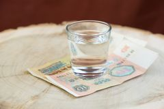 Viejas 10 rublos de URSS en la tabla debajo de un vidrio de vodka, fondo rojo Fotografía de archivo libre de regalías