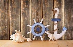 Viejas rueda, ancla y cáscaras de madera náuticas en la tabla de madera sobre fondo de madera imagen filtrada vintage imagen de archivo