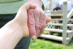 Viejas y jovenes manos en patio trasero Imagenes de archivo