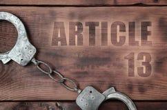 Viejas y oxidadas esposas de la policía e inscripción del artículo 13 fotografía de archivo libre de regalías