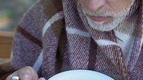 Viejo abuelo que come lentamente las gachas de avena, comidas de la caridad para los pensionistas pobres almacen de metraje de vídeo