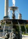 Viejo adorno de la ciudad con la fuente de la primavera con las figuras y la torre del pilar y del castillo en el fondo imagenes de archivo