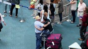 Viejo amigo dos que abraza junto en el pasillo internacional de la llegada metrajes