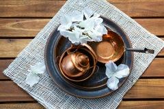 Viejo artículos de cocina rasguñado de cobre de la loza del vintage en la tabla foto de archivo