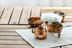 Viejo artículos de cocina rasguñado de cobre de la loza del vintage en la tabla fotografía de archivo
