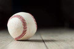 Viejo béisbol en fondo y altamente el primer de madera Imagenes de archivo