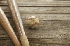 Viejo béisbol y palos en superficie de madera áspera Foto de archivo libre de regalías