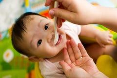 viejo bebé asiático de 6 meses que es introducido el cereal Fotografía de archivo libre de regalías