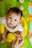 viejo bebé asiático de 6 meses que es introducido el cereal Imágenes de archivo libres de regalías