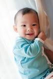 viejo bebé asiático de 7 meses que sonríe y que se sostiene encendido Foto de archivo libre de regalías