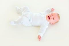 Viejo bebé cuatrimestral gritador que pone encendido detrás Fotografía de archivo libre de regalías