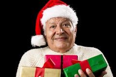 Viejo caballero desconcertado que lleva tres regalos envueltos Imagen de archivo