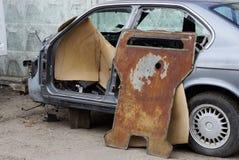Viejo coche desmontado del coche marco gris con las partes oxidadas en la calle cerca de la cerca foto de archivo