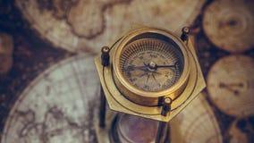 Viejo compás del reloj de arena en mapa del mundo fotos de archivo libres de regalías