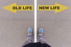 Viejo contra nuevas flechas del texto de la vida en la tierra, los pies y los zapatos del asfalto encendido Fotos de archivo