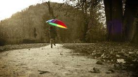 Viejo efecto de la película: el feliz niño pequeño salta en un parque otoñal con el paraguas de varios colores almacen de metraje de vídeo