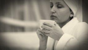Viejo efecto de la película: La muchacha bonita bebe el café de la mañana almacen de video