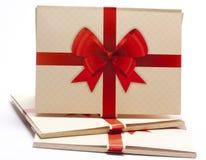 Viejo embalaje de papel con la cinta roja y el arco rojo Imagen de archivo libre de regalías
