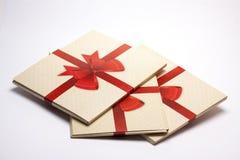 Viejo embalaje de papel con la cinta roja y el arco rojo Fotos de archivo libres de regalías