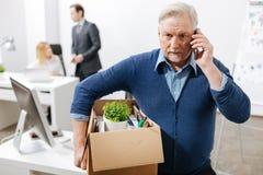 Viejo empleado desconcertado que sale de la oficina con la caja llena de pertenencia foto de archivo