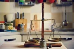 Viejo equilibrio en la tabla de madera en fondo de la cocina Fotografía de archivo