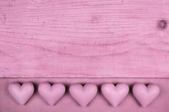 Viejo fondo de madera rosado con cinco corazones para una tarjeta de felicitación Fotografía de archivo