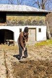 Viejo granjero con el funcionamiento del rastrillo imagen de archivo libre de regalías