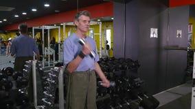 Viejo hombre activo que hace ejercicio con pesas de gimnasia en un gimnasio almacen de metraje de vídeo