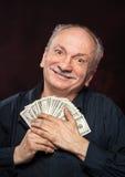 Viejo hombre afortunado con las cuentas de dólar Fotografía de archivo