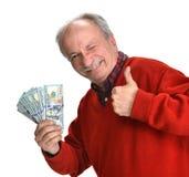 Viejo hombre afortunado que lleva a cabo billetes de dólar Fotografía de archivo