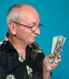 Viejo hombre afortunado que lleva a cabo billetes de dólar Foto de archivo libre de regalías