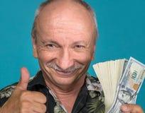 Viejo hombre afortunado que lleva a cabo billetes de dólar Imágenes de archivo libres de regalías