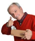 Viejo hombre afortunado que sostiene la caja con los billetes de dólar Fotos de archivo