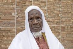 Viejo hombre africano que se sienta delante de su casa, ochenta años Imagen de archivo libre de regalías