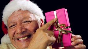 Viejo hombre alegre que muestra un regalo envuelto rosa de Navidad almacen de metraje de vídeo