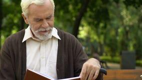 Viejo hombre arrugado con el bastón que se sienta en banco y el libro de lectura en el parque verde metrajes