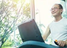 Viejo hombre asiático que corre en una rueda de ardilla Foto de archivo libre de regalías