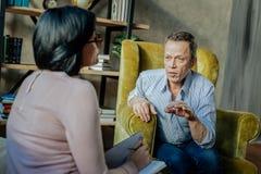 Viejo hombre comunicativo en camisa ligera que habla con el especialista foto de archivo libre de regalías