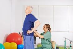 Viejo hombre con dolor de espalda en fisioterapia fotos de archivo libres de regalías