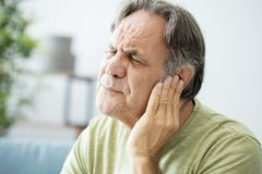 Viejo hombre con dolor de oído foto de archivo