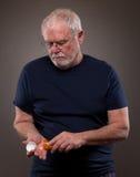 Viejo hombre con el hombre del bottleOld de las píldoras con la botella de píldoras Fotografía de archivo libre de regalías