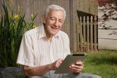 Viejo hombre con el ordenador de la tablilla Imagenes de archivo