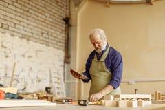 Viejo hombre con el pelo, el bigote gris y la barba trabajando con la tableta en el garaje fotos de archivo