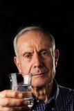 Viejo hombre con el vidrio de agua Foto de archivo libre de regalías